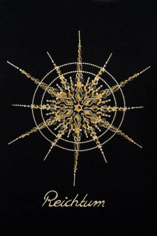 Kristall Reichtum gestickt auf schwarzem T-Shirt Großaufnahme