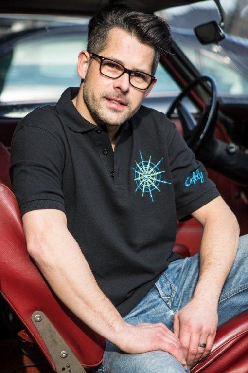 Poloshirt für Männer schwarz mit Kristall Erfolg gestickt in Blautönen sitzend im Auto
