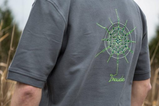 Kristall Freude gestickt auf grauem Polo-Shirt Großaufnahme