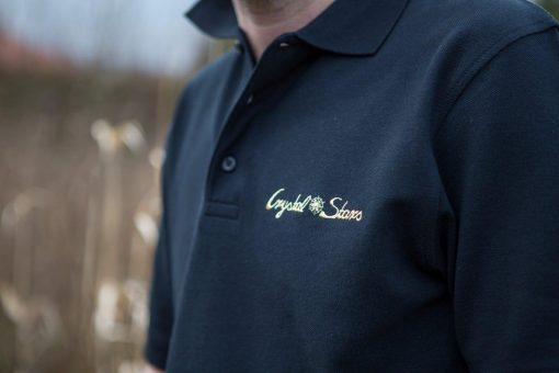 Logo Crystal Stars gestickt in Gold auf einem schwarzen Polo Shirt für Männer
